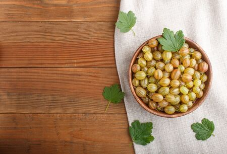 Fresh green gooseberry in wooden bowl on wooden background. top view, flat lay, copy space. Stock fotó