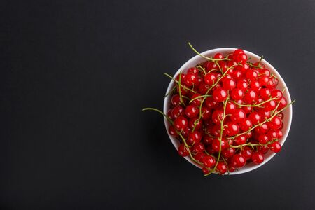 Fresh red currant in white bowl on black background. top view, flat lay, copy space.