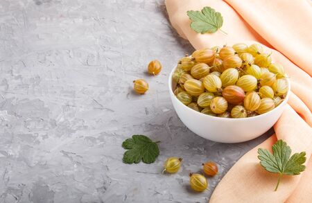 Fresh green gooseberry in white bowl with orange textile on gray concrete background. side view, copy space. Stock fotó