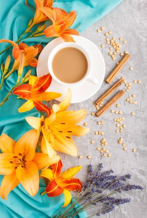 Orange day-lily and lavender flowers and a cup of coffee on a gray concrete background, with blue textile. Morninig, spring, fashion composition. Flat lay, top view,