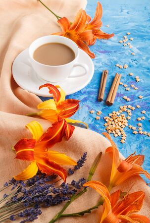 Orange day-lily and lavender flowers and a cup of coffee on a blue concrete background, with orange textile. Morninig, spring, fashion composition. side view.