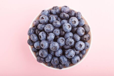 Fresh blueberry in white bowl on  pink background. top view, close up, flat lay. Stock fotó