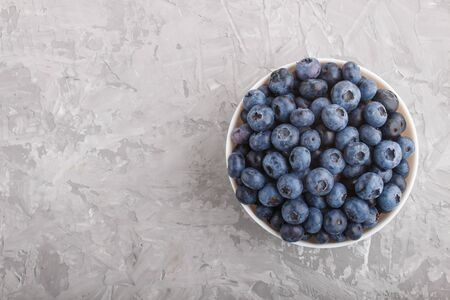 Fresh blueberry in white bowl on gray concrete background. top view, flat lay, copy space. Stock fotó