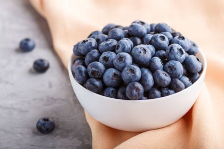 Fresh blueberry in white bowl and orange pastel textile on gray concrete background. side view, close up, selective focus.