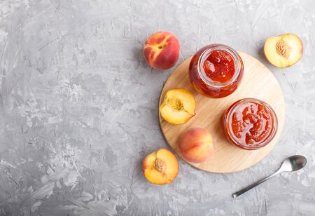 Peach jam in a glass jar with fresh fruits on gray concrete background. top view, flat lay, copy space.