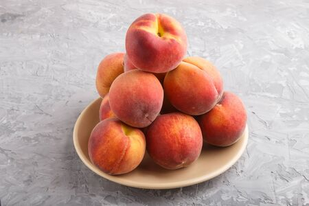 Fresh peaches on a plate on gray concrete background. side view, close up.