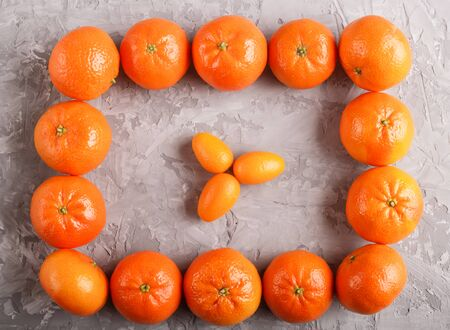 Rows of tangerines forming a rectangle and and three kumquats inside on a gray concrete background, top view, flat lay. Stock fotó