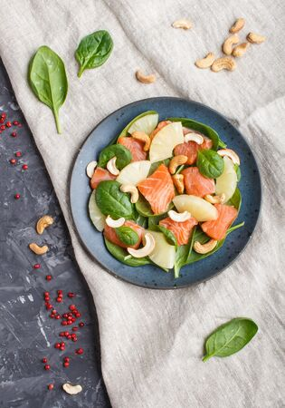Fresh salmon with pineapple, spinach and cashew  on a black concrete background. Top view, flat lay, linen tablecloth. Stock fotó