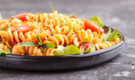 Fusilli pasta with tomato sauce, cherry tomatoes, lettuce and herbs on a black concrete background. side view, close up. Stock fotó