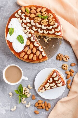 Homemade cake with caramel cream and nuts with cup of coffee on a gray concrete  background. top view. flat lay, copy space. Stock fotó