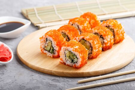 Japanese maki sushi rolls with flying fish roe, chopsticks, soy sauce and marinated ginger on wooden board on a gray concrete background. Side view, close up, selective focus. Stock fotó