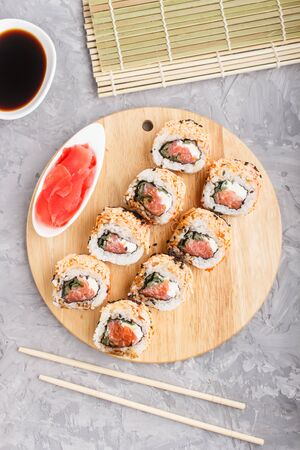 Japanese maki sushi rolls with salmon, sesame, chopsticks, soy sauce and marinated ginger on wooden board on a gray concrete background. Top view, flat lay.