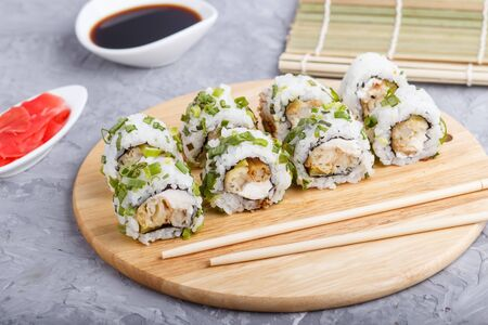 Japanese maki sushi rolls with green onion, chopsticks, soy sauce and marinated ginger on wooden board on a gray concrete background. Side view, close up, selective focus. Stock fotó