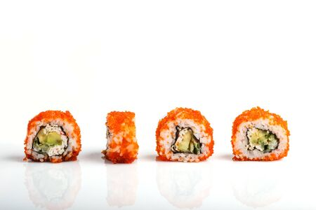 Four Japanese maki sushi rolls in a row with flying fish roe, avocado, and cucumber isolated on white background. Side view, close up.
