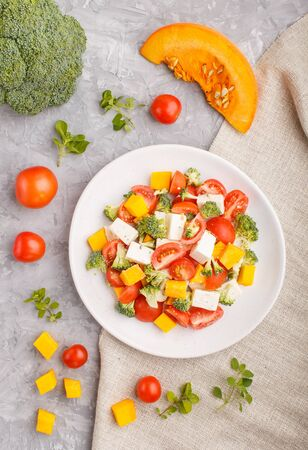 Vegetarian salad with broccoli, tomatoes, feta cheese, and pumpkin on white ceramic plate on a gray concrete background and linen textile, top view, close up, flat lay.
