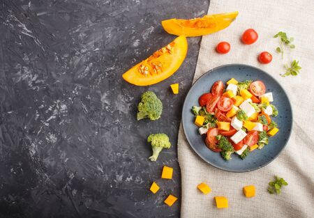 Vegetarian salad with broccoli, tomatoes, feta cheese, and pumpkin on a blue ceramic plate on a black concrete background and linen textile, top view, copy space, flat lay.