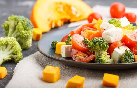 Vegetarian salad with broccoli, tomatoes, feta cheese, and pumpkin on a blue ceramic plate on a black concrete background and linen textile, side view, close up, selective focus. Stock fotó