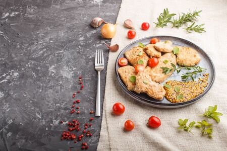 Fried pork chops with tomatoes and herbs on a gray ceramic plate on a black concrete Stock fotó
