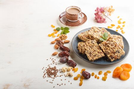 Homemade granola from oat flakes, dates, dried apricots, raisins, nuts in blue ceramic plate with a cup of coffee on a white wooden background. Side view, copy space.