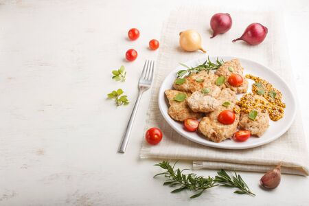 Fried pork chops with tomatoes and herbs on a white ceramic plate on a white wooden Stock fotó