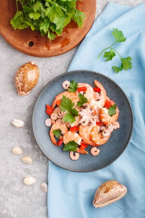 Boiled shrimps or prawns and small octopuses with herbs on a blue ceramic plate on a gray concrete background and blue textile. Top view, flat lay, close up.