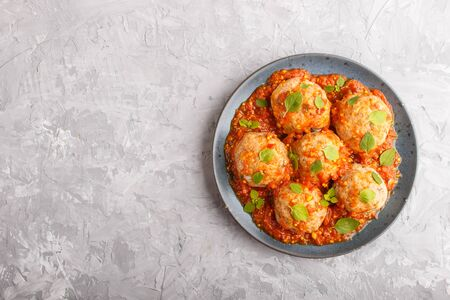 Pork meatballs with tomato sauce, oregano leaves, spices and herbs on blue ceramic plate on a gray concrete
