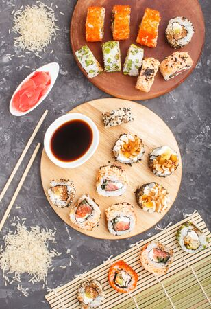 Different kinds of maki sushi rolls with salmon, sesame, cheese, roe and chopsticks, soy sauce, marinated ginger on a black concrete background. Top view, flat lay, close up. Japanese food concept.