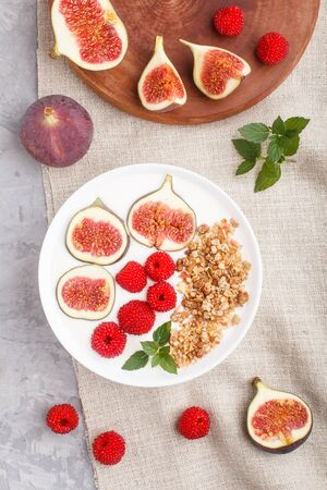 Yoghurt with raspberry, granola and figs in white plate on a gray concrete background and linen textile. top view, flat lay, close up.