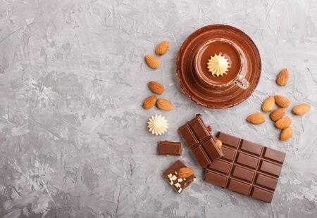 グレーのコンクリートの背景にアーモンドとホットチョコレートとミルクチョコレートのカップ。フラットレイ、トップビュー、コピースペース。