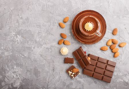 Cup of hot chocolate and pieces of milk chocolate with almonds on a gray concrete background. Flat lay, top view, copy space.