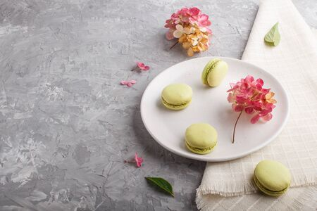 Green macarons or macaroons cakes on white ceramic plate on a gray concrete background and linen textile. side view, copy space.