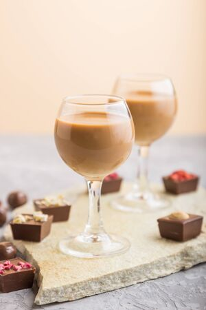 Sweet chocolate liqueur in glass with chocolate candies on a gray concrete