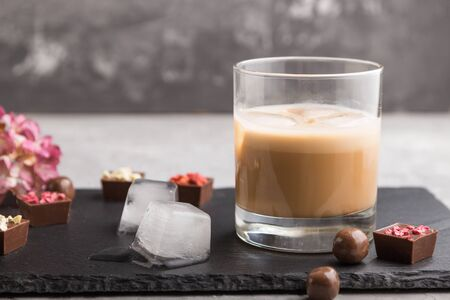 Sweet chocolate liqueur with ice in glass with chocolate candies on a gray concrete