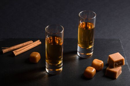 Glass of whiskey with caramel candies on a black stone slate board on black