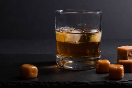 Glass of amber whiskey with ice and caramel candies on a black stone slate board on black background. Side view, close up, low key concept. Stock Photo