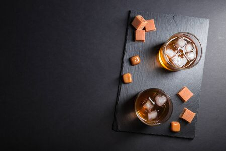 Glass of amber whiskey with ice and caramel candies on a black stone slate board on black