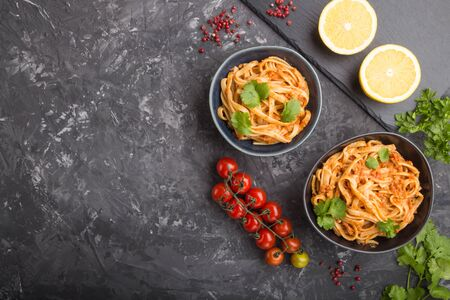 Semolina pasta with tomato pesto sauce, orange and herbs in bowls on a black concrete
