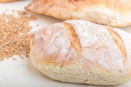 Diversi tipi di pane appena sfornato su uno sfondo di legno bianco. vista laterale, primo piano.