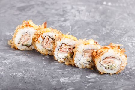 Japanese maki sushi rolls with tuna, cucumber, cheese on black concrete background. Side view, close up, copy space.
