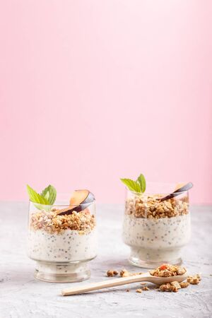 Yoghurt with plum, chia seeds and granola in a glass and wooden spoon on gray and pink background. side view, close up.