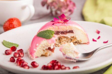 グレーのコンクリートの背景と緑の織物にイチゴとコーヒーのカップとピンクのムースケーキ。サイドビュー、クローズアップ、選択的フォーカス、噛み切る。