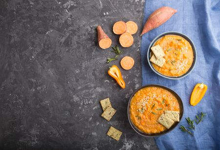 Sweet potato or batata cream soup with sesame seeds and snacks in blue ceramic bowls on a black concrete