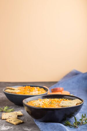 Sweet potato or batata cream soup with sesame seeds and snacks in blue ceramic bowls