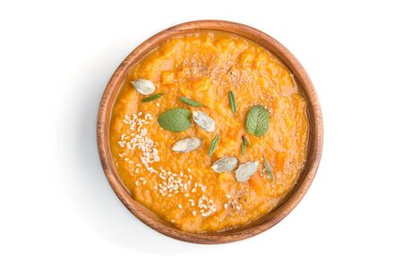 Sweet potato or batata cream soup with sesame seeds in a wooden bowl isolated on a white