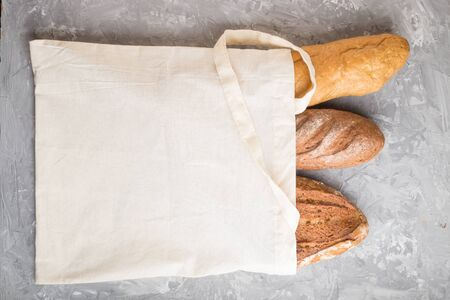 Reusable textile grocery bag with fresh baked bread on a gray concrete