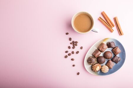 Different chocolate candies and a cup of coffee on a pink pastel
