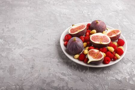 Fresh figs, strawberries and raspberries on white ceramic plate on gray concrete