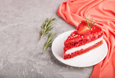 Homemade red velvet cake with milk cream and strawberry on a gray concrete background with red textile. side view, copy space, selective focus. Reklamní fotografie
