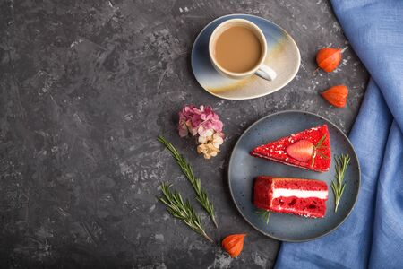 Homemade red velvet cake with milk cream and strawberry  with cup of coffee on a black Reklamní fotografie