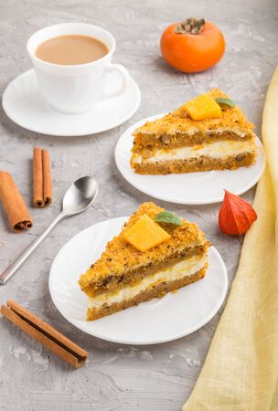Homemade cake with persimmon and pumpkin and a cup of coffee on a gray concrete background with yellow textile. side view, close up. Reklamní fotografie
